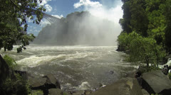 Mist with large cliff behind framed by tropical trees and flowing Zambezi River Stock Footage