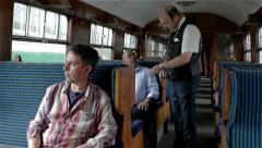 British Railway: Train ticket inspector checking passenger tickets in carriage Stock Footage