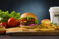 Hamburger fast food with plenty of raw materials on the background Stock Photos