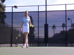 A lady in tennis court is hitting the ball on ground and serving it Stock Footage