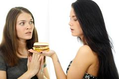 two girls divide one sandwich - stock photo