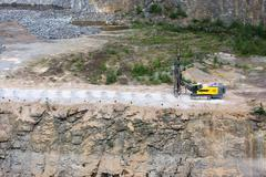 Drilling machine in open cast mining quarry Stock Photos