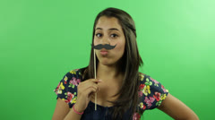A girl with mustache stick at the green screen background Stock Footage
