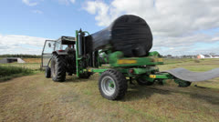 Tractor wrapping bail of hay - stock footage