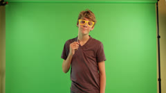 A boy at the green screen background is holding nose glass stick mask Stock Footage
