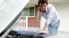 Man trying to fix smoking car in front of house - stock footage