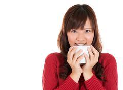 asian woman drinking coffee or tea - stock photo