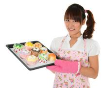 Stock Photo of young asian girl baking bread and cupcakes