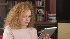 Young girl sitting in the room with tablet computer, tracking shot HD Stock Footage