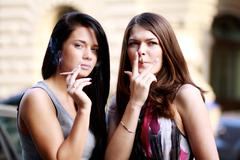 two young women smoking cigarettes on the street - stock photo
