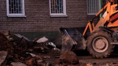 Tractor on building removes garbage, stones, sand Stock Footage