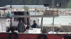 Reloading fish from boat on truck 2 Stock Footage