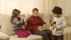 Father is trying to work on lap top, while his children are having fun. - stock footage
