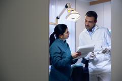 Hammaslääkäri ja avustaja asiakirjojen tarkastaminen hammashoidon studiossa Kuvituskuvat