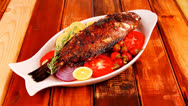 Stock Video Footage of main course: whole fryed sunfish on wood