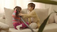 Children having fun playing with vacuum cleaner. Stock Footage