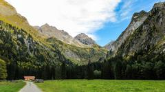 alpine valley with road and hut - stock photo