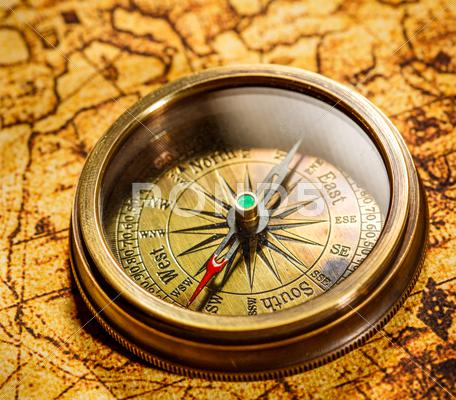 Stock photo of vintage compass lies on an ancient world map.