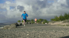 Young couple jogging on the beach, slow motion shot at 120fps Stock Footage
