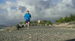 Young couple jogging on the beach, slow motion shot at 60fps Stock Footage