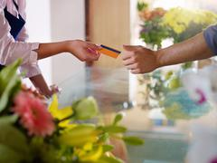 Client with credit card shopping in flowers shop Stock Photos