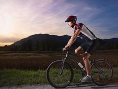 young man training on mountain bike at sunset - stock photo