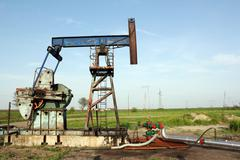 oilfield with pump jack and pipeline - stock photo