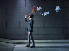 Businessman throwing away files and documents Stock Photos