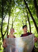 young couple looking at map during trek - stock photo