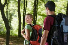 Couple with backpack doing trekking in wood Stock Photos
