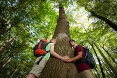 environmental conservation: young hikers embracing large tree - stock photo
