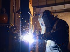 man at work as welder in heavy industry - stock photo