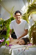 Masseur at work massaging woman in luxury spa Stock Photos