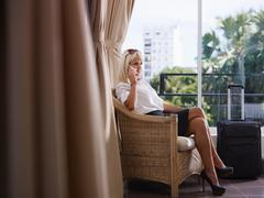 Businesswoman using mobile phone in hotel room Stock Photos