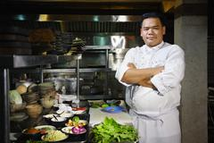 asian chef smiling at camera in restaurant kitchen - stock photo