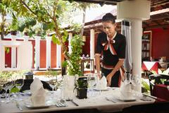 Asian waitress setting table in restaurant Stock Photos