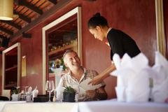 asian waitress talking with client in restaurant - stock photo