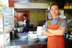 Man working as cook in asian restaurant kitchen Stock Photos