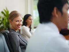 Businesspeople talking in meeting room and woman smiling Stock Photos