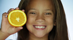 A young Teenage kid holds lemon in her hand grin Stock Footage