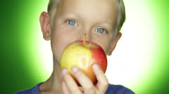 A young toddler holds an apple in his hand with the grin Stock Footage