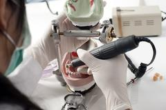 dental technician working with articulator - stock photo