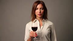 A young white lady holds the wine glass in her hand and smiles Stock Footage