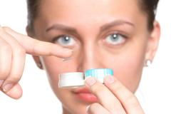 contact lenses box in womans hand - stock photo