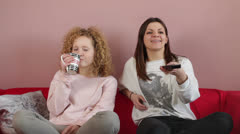 Young smiling girls watching TV together  HD Stock Footage
