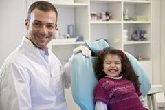portrait of child and dentist in dental studio, looking at camera - stock photo