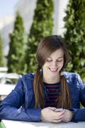 young woman reading a message on the phone - stock photo