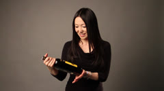 A youthful lady with wine bottle gives to an advert - stock footage