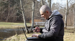 Man with cell phone, PC on a bench near river in park Stock Footage