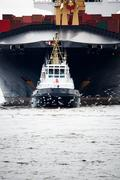 tugboat pulling freighter - stock photo